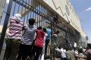 Protesters climb a fence surrounding the U.S. embassy in Sanaa