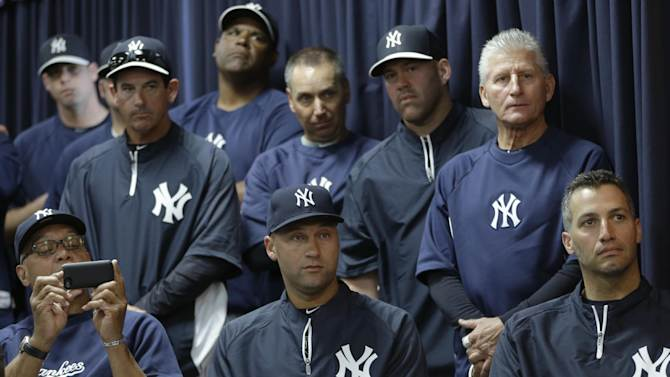 Hall of Famer Reggie Jackson, far left,  snaps a photo as he sits beside New York Yankees shortstop Derek Jeter, center, and pitcher Andy Pettitte, right, as they watch Yankees pitcher Mariano Rivera, who holds baseball's all-time saves record, announce his plans to retire at the end of the 2013 season during a news conference at Steinbrenner Field Saturday, March 9, 2013 in Tampa, Fla. (AP Photo/Kathy Willens)