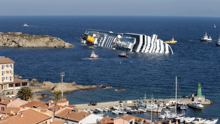 FILE - This Jan. 14, 2012 file photo shows the luxury cruise ship Costa Concordia leaning on its starboard side after running aground on the tiny Tuscan island of Giglio, Italy. Franco Gabrielli, who heads the Civil Protection Department overseeing the wreck's removal, told reporters on Giglio Island Sunday, July 13, 2014, that while weather conditions aren't optimal, they are good enough to permit the start of operations to refloat and tow the Concordia to Genoa on the mainland for scrapping. He also promised that a search will be conducted for the only unrecovered body of the 32 Costa Concordia shipwreck victims as soon as the wrecked cruise liner is towed away from the island where it struck a reef in 2012. (AP Photo/Gregorio Borgia, File)
