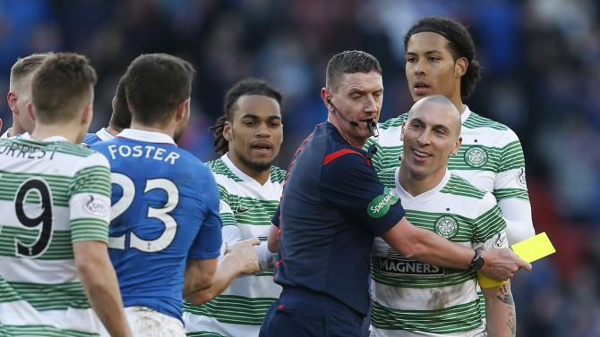 Referee Craig Thomson holds Celtic's Scott Brown away from Rangers' Richard Foster before booking him during their Scottish League Cup semi final soccer match  at Hampden Park stadium in Glasgow, Scotland