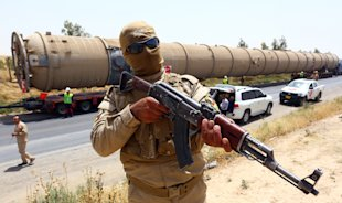 A Kurdish peshmerga fighter stands guard as new equipment arrives at Kalak refinery on the outskirts of Irbil, Iraq, Monday, July 14, 2014, as Kurdish...