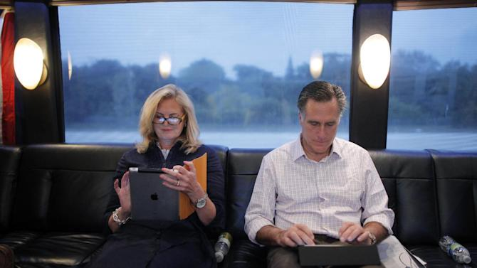 """FILE-  In this Jan. 29, 2012, file photo, Republican presidential candidate, former Massachusetts Gov. Mitt Romney, and his wife Ann work on their iPads on their campaign bus as it travels to Hialeah, Fla. The spotlight on Ann Romney is getting brighter. Two out of three voters still don't know the wife of the presumptive Republican presidential nominee. But her profile is growing as Mitt Romney moves into the general election against President Barack Obama. She was a stay-at-home mother of five boys. She bakes cookies. And, at 63, she has 16 grandchildren who call her """"Mamie."""" But don't be fooled: Republicans and Democrats alike see Ann Romney as an effective political weapon. (AP Photo/Charles Dharapak, File)"""