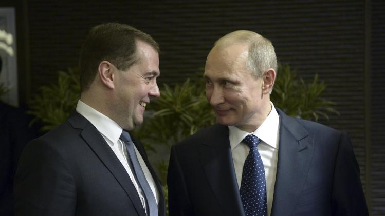 Russia's President Vladimir Putin talks to Prime Minister Dmitry Medvedev before the opening ceremony of the 2014 Paralympic Winter Games in Sochi