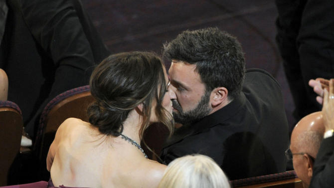 """Jennifer Garner, left, kisses husband and director Ben Affleck after """"Argo"""" is announced the winner for the award for best picture during the Oscars at the Dolby Theatre on Sunday Feb. 24, 2013, in Los Angeles.  (Photo by Chris Pizzello/Invision/AP)"""