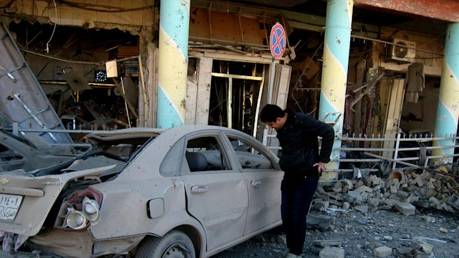 A man inspects his destroyed car at the scene of a bomb attack in Kirkuk, 180 miles (290 kilometers) north of Baghdad, Iraq, Wednesday, Jan. 16, 2013. Two car bombs exploded in Kirkuk, the deadliest of the two explosions struck the local headquarters of the Kurdistan Democratic Party. The KDP is led by Massoud Barzani, the president of Iraq's largely autonomous Kurdish region, who has frequently sparred with Iraq's central governor in Baghdad, killing and wounding scores of people, police said. (AP Photo/Emad Matti)