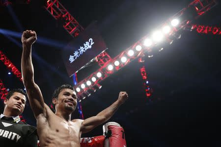 Manny Pacquiao of the Philippines celebrates his victory over Chris Algieri of the U.S. during their World Boxing Organisation 12-round welterweight title fight in Macau