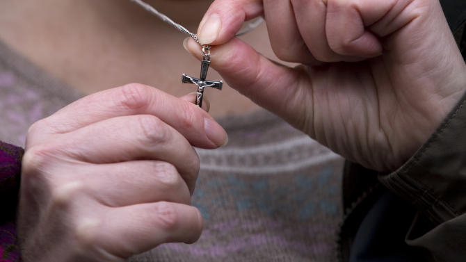 Shirley Chaplin poses for photographs while holding her crucifix necklace before a press conference in London, Tuesday, Jan. 15, 2013.  Europe's highest court ruled Tuesday against Shirley Chaplin, a nurse who was told to remove a crucifix necklace at work, rejecting the religious discrimination case, with the judges saying Chaplin's employer banned necklaces on health and safety grounds, and so asking her to remove the symbol was not excessive.  (AP Photo/Matt Dunham)