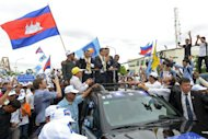 Leader of the opposition Cambodia National Rescue Party (CNRP) Sam Rainsy (centre R) greets supporters in Phnom Penh on July 19, 2013. Rainsy lost his bid to regain lawmaker status Thursday in a new setback to his efforts to challenge strongman premier Hun Sen in this weekend's election