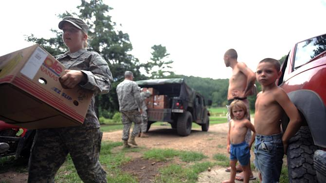 Spc. Megan Pena, left, with the W.Va. National Guard, carries a box of food to a home in Heaters, W.Va., as Austin Hefner, 7, right, Brianna Dunbar, 4, center, and Billy Dunbar Jr., 25,  watch Thursday, July 5, 2012. While utility crews continued working to restore power, members of the West Virginia National Guard went door to door with firefighters, police, church groups and others to reach people who were still awaiting help. Residents in the Heaters area have been without power since Friday, June 29, 2012 following a severe storm. (AP Photo/Jeff Gentner)