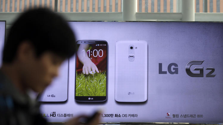 A man uses his mobile phone near a banner advertising LG Electronics' G2 smartphone at downtown Seoul, South Korea, Thursday, Oct. 24, 2013. LG Electronics Inc. said third quarter profit slid 34 percent as it cut prices and spent more on marketing to carve out a share of the high-end smartphone market. (AP Photo/Lee Jin-man)