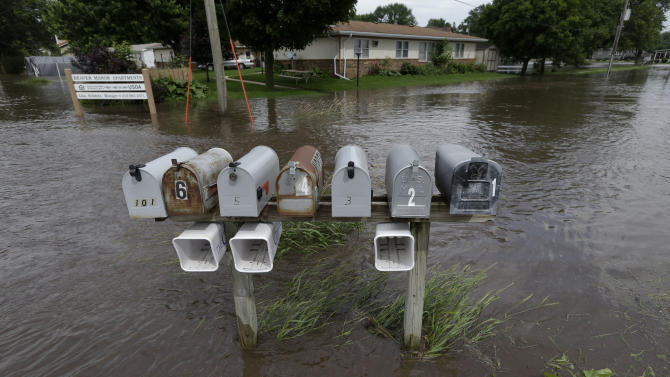 Mailboxes are surrounded by floodwaters in front of a home, Tuesday, June 25, 2013, in New Hartford, Iowa. Hundreds of residents obeyed an order to evacuate their homes in this northeast Iowa town Tuesday before floodwaters from a rising creek could strand them. (AP Photo/Charlie Neibergall)