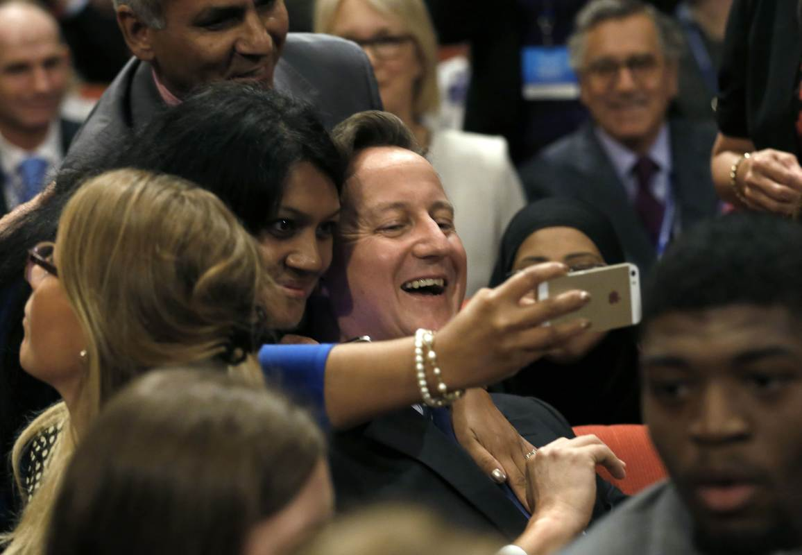 Britain's Prime Minister David Cameron smiles as he has a selfie photograph taken during the Conservative Party Conference in Birmingham