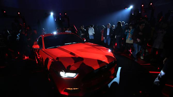 FILE - In this Thursday, Dec. 5, 2013, file photo, guests look at the latest Mustang of the Ford Motor Company which is being unveiled at the All-New Ford Mustang Global Reveal event in Shanghai, China. Ford Motor Co. warned of tough price competition and harder-to-reach profit targets Wednesday, DEc. 18, 2013, a sign that the company and the auto industry face a tougher road after four years of robust recovery from the Great Recession. (AP Photo/Eugene Hoshiko, File)