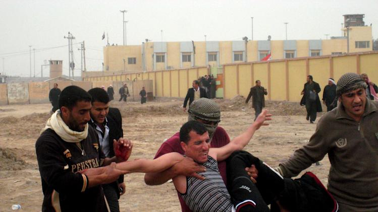 Protesters carry an injured man during clashes in Fallujah, 40 miles (65 kilometers) west of Baghdad, Iraq, Friday, Jan. 25, 2013. Iraqi troops shot dead five protesters Friday as they opened fire at stone-hurling demonstrators angry at the troops for preventing them from joining an anti-government rally west of Baghdad, officials said. (AP Photo/ Bilal Fawzi)