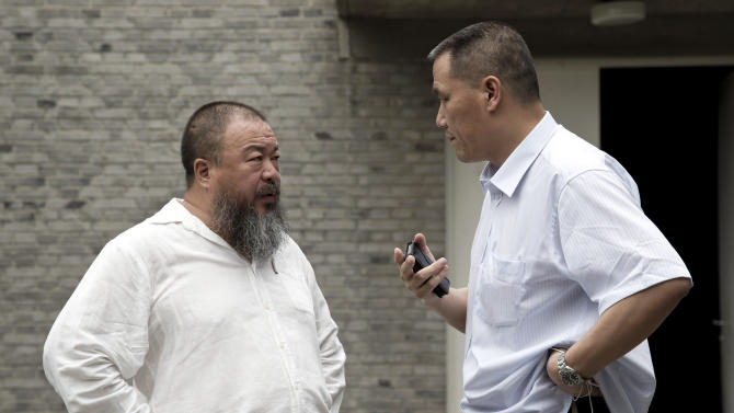 Ai Weiwei, left, talks with his lawyer Pu Zhiqiang at his house's courtyard in Beijing Wednesday, June 20, 2012. Chinese police on Wednesday barred Ai from attending the first hearing of a lawsuit brought by his company against Beijing tax authorities and blocked reporters from filming at the courthouse, part of an intimidation campaign aimed at silencing the prominent artist and outspoken government critic. (AP Photo/Andy Wong)