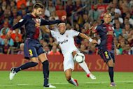 Barcelona's defender Gerard Pique (L) and Real Madrid's German midfielder Mesut Ozil (C) battle over the ball during their Spanish Supercup match on August 23, 2012 at the Camp Nou stadium in Barcelona