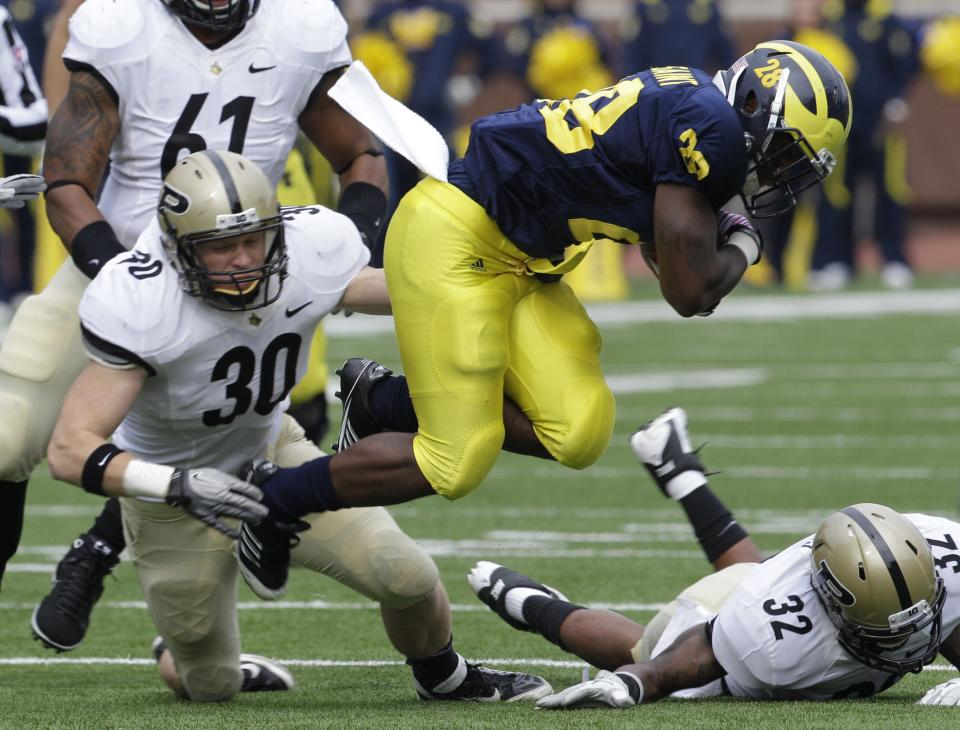 Michigan running back Fitzgerald Toussaint (28) is stopped by Purdue linebacker Joe Holland (30) and safety Albert Evans (32) during the second quarter of an NCAA college football game in Ann Arbor, Mich., Saturday, Oct. 29, 2011. (AP Photo/Carlos Osorio)