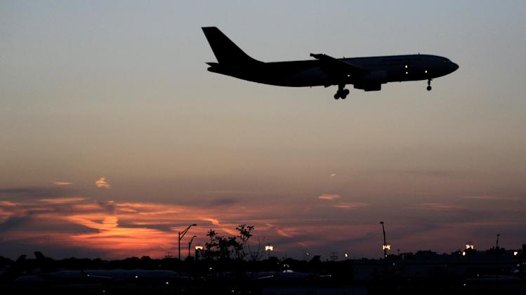 FILE- In this April 25, 2012, file photo, an airplane lands at Newark Liberty International Airport in Newark. More travelers are flying than ever before, creating a daunting challenge for airlines: continue to keep passengers safe in an ever more crowded airspace. (AP Photo/Julio Cortez, File)