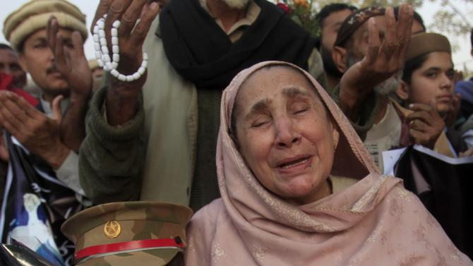 A woman weeps for victims in front of Army Public School which was attacked by Taliban gunmen, in Peshawar