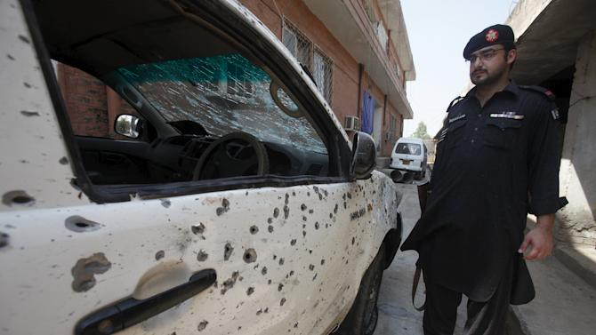 A security official stands next to a vehicle damaged in a suicide attack in Jamrud
