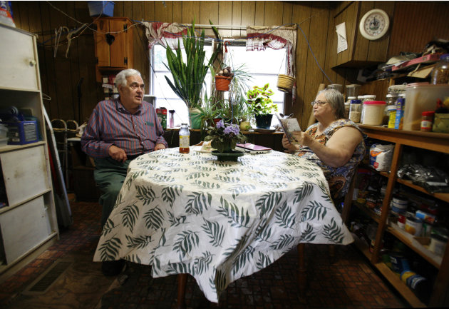 In this Sept. 15, 2011 photo, Bill Ricker talks with his ex-wife Judith Odyssey in the trailer home they share, in Hartford, Maine. They divorced around 1995 and she moved out. But he offered to let h
