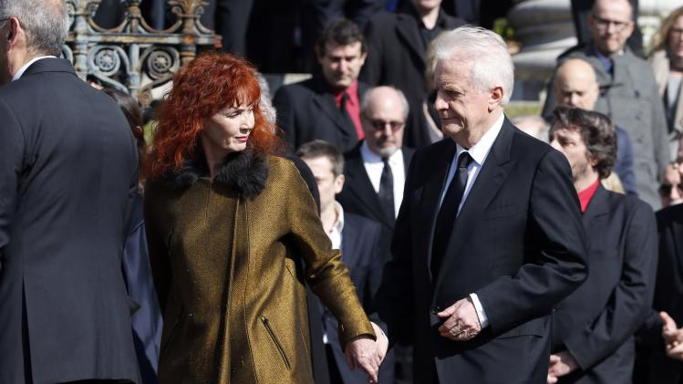 French actress Sabine Azema and actor Andre Dussollier leave after the funeral ceremony of late film director Alain Resnais at the Saint-Vincent-de-Paul church in Paris