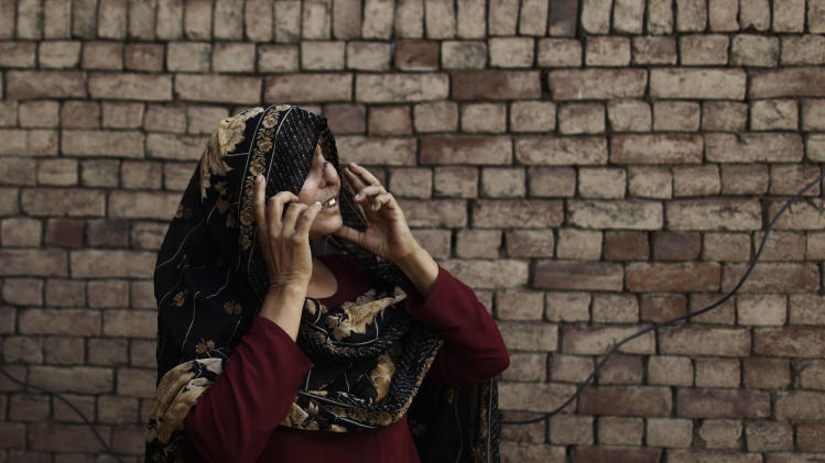 """In this Thursday, May 10, 2012 photo, Pakistani Allah Rakhi, 51, whose nose was sliced by her husband, adjusts her scarf at her home in  Thatha Pira, near Gujranwala, Pakistan. Allah Rakhi's husband sliced of her nose and right foot with a razor in 1980, when she was 19. The nose has special significance in Pakistani culture, where it symbolizes the honor of the family. A popular plea from parents to children is """"Please take care of our nose"""", which means """"don't do anything that tarnishes the name of the family."""" (AP Photo/Muhammed Muheisen)"""