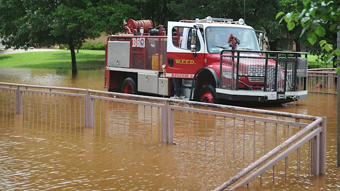 In this May 24, 2015 photo, a Wichita Falls, Texas firefighter reaches out of his truck to measure the depth of the water on Ridgemont where the Wichita River backs into Tanglewood Lake. In the U.S., the weather system dumped record rainfall on parts of the Plains and Midwest, spawning tornadoes and causing major flooding that forced at least 2,000 Texans from their homes. (Torin Halsey/Times Record News via AP)