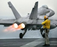 A US Navy F-/A-18C Hornet takes off from the USS Kitty Hawk in northern Gulf waters on March 25, 2003