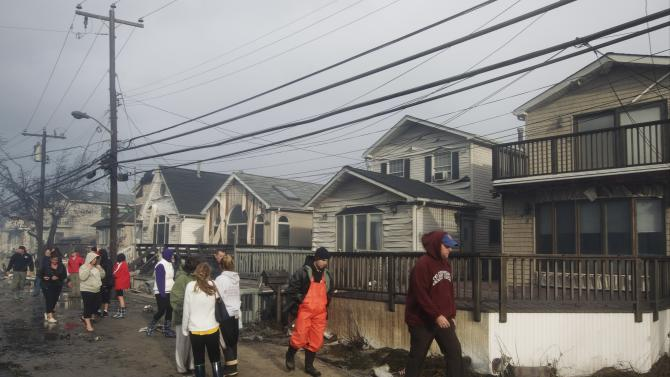 Residents assess damage caused by a fire at Breezy Point, in the New York City borough of Queens Tuesday, Oct. 30, 2012, in New York. The fire destroyed between 80 and 100 houses Monday night in the flooded neighborhood. More than 190 firefighters have contained the six-alarm blaze fire, but they are still putting out some pockets of fire. (AP Photo/Frank Franklin II)