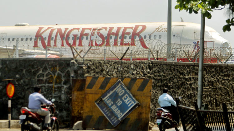 Commuters drive past a stationary aircraft belonging to Kingfisher airlines at the domestic airport in Mumbai, India, Tuesday, March 20, 2012. The severely cash-strapped airlines may now face the risk of cancellation of its flying permit after the Directorate General of Civil Aviation (DGCA) expressed doubts on its ability to maintain a steady schedule with a declining number of operable aircrafts and ongoing problems with pilots leaving the company.(AP Photo/Rafiq Maqbool)