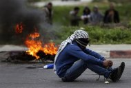 A protester sits next to a burning tire during clashes with Israeli troops outside Israel's Ofer military prison near the West Bank city of Ramallah February 22, 2013. Israeli forces clashed with Palestinian protesters throughout the occupied West Bank on Friday, capping a week of violence amid a hunger strike by four Palestinians in Israeli jails. REUTERS/Mohamad Torokman