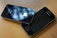 A Samsung phone (R) and an Apple iPhone 4 are shown. South Korea's Samsung Electronics said it was considering adding Apple's new iPhone 5 to a patent infringement case as part of a long-running global legal battle between the rival smartphone giants