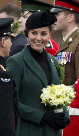 Britain's Kate the Duchess of Cambridge holds flowers after presenting traditional sprigs of shamrocks to members of the 1st Battalion Irish Guards at the St Patrick's Day Parade at Mons Barracks in Aldershot, England, Sunday, March 17, 2013. Kate presenting the sprigs of shamrocks to the regiment Sunday, follows a century-old tradition inaugurated by Queen Alexandra, the wife of the then King, Edward VII back in 1901. (AP Photo/Matt Dunham)