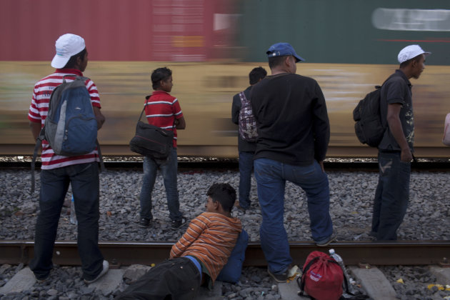 In this May 17, 2012 photo, migrants, mostly from Honduras, watch a southbound train pass by as they wait for one going north, in Lecheria, on the outskirts of Mexico City. While the number of Mexican