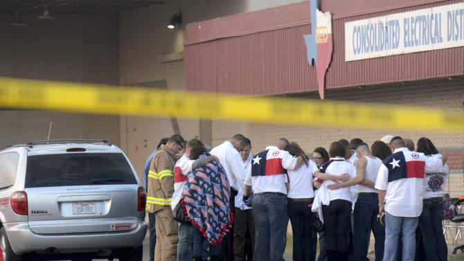 Parade participants and public safety officials huddle after a trailer carrying wounded veterans in a parade was struck by a train in Midland, Texas, Thursday, Nov. 15, 2012. Authorities say four people are dead and 17 others are injured after a Union Pacific train slammed into the parade float.  (AP Photo/Reporter-Telegram, James Durbin)