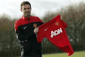 Manchester United's new signing Mata holds a club shirt during a photocall at the club's Carrington training complex in Manchester