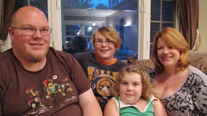 This July 11, 2011 picture shows Xavier Montjoy, center, with his father, Greg, left, younger sister, Isabella, and mother, Nikki, at their home in Columbus, Ohio. Xavier was born hours before the terror attacks on Sept. 11, 2001. Like millions of children born in the past decade, Xavier has never known a world untouched by that day's terror attacks. He's played baseball and soccer and hates math like generations before him but is growing up in a new normal. In this world, Afghanistan has always been a place of war, and several of his relatives in the military have been deployed overseas. Border security was tightened, and there are travel restrictions that hamper family trips and force travelers to stand in security lines in socks or bare feet at the airport near his house on a tree-lined Columbus street. (AP Photo/Kantele Franko)