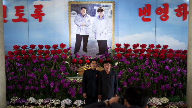 """FILE -  In this Friday, April 12, 2013 file photo, two men hold hands as they pose for photos in front of a portrait of the late North Korean leader Kim Jong Il, right, and his son Kim Jong Un at a flower show featuring thousands of Kimilsungia flowers, named after the late leader Kim Il Sung, in Pyongyang, North Korea. Enemy capitals, North Korea said, will be turned """"into a sea of fire."""" North Korea's first strikes will be """"a signal flare marking the start of a holy war.""""  Pyongyang's nuclear arsenal is """"mounted on launch pads, aimed at the windpipe of our enemies."""" And it's not all talk. The profoundly isolated, totalitarian nation has launched two rockets over the past year. But there is also a logic behind North Korea's behavior, a logic steeped in internal politics, one family's fear of losing control and the ways that a weak, poverty-wracked nation can extract concessions from some of the world's most fearsome military powers. (AP Photo/Alexander F. Yuan, File)"""