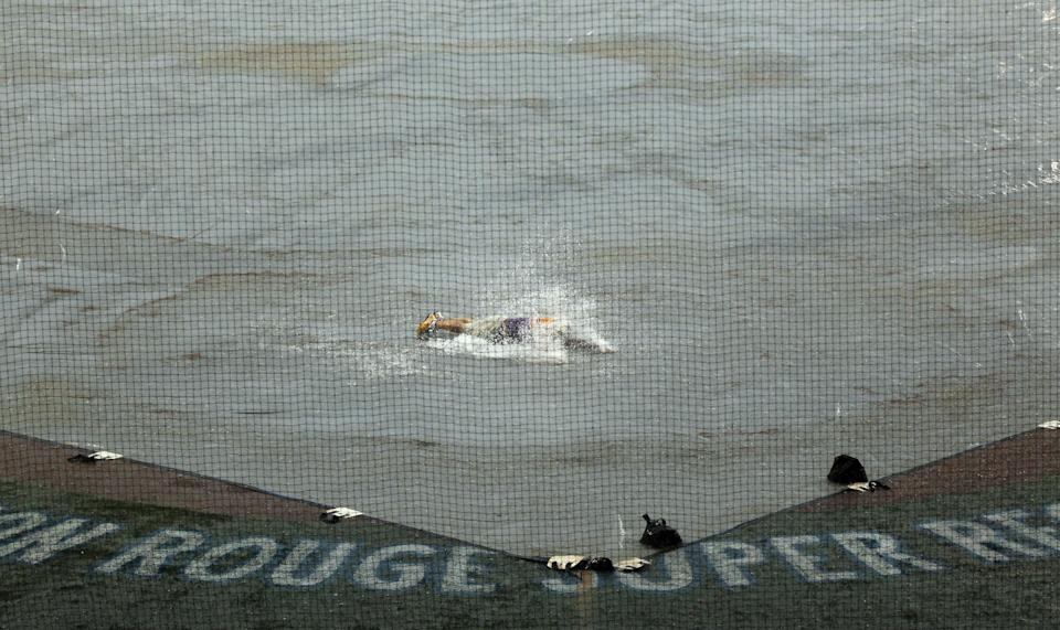 A fan slides across the rain-covered tarp during a weather delay in an NCAA college baseball tournament super regional game between Stony Brook and LSU in Baton Rouge, La., Friday, June 8, 2012. (AP Photo/Gerald Herbert)
