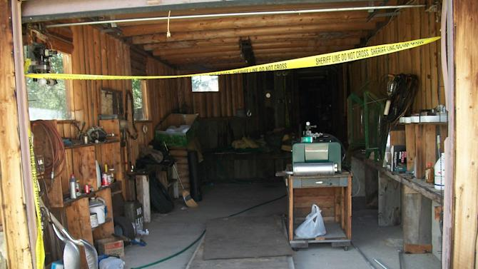 A September, 2014,  photo released by the Chaffee County Sheriff's Office is of the garage at home of Edwin Bartheld in the ghost town of Turret, Colo.  Bartheld's body was found surrounded by explosive in a crawl space under his house.  The crawl space is entered through the wall at right.  (AP Photo/Chaffee County Sherriff)