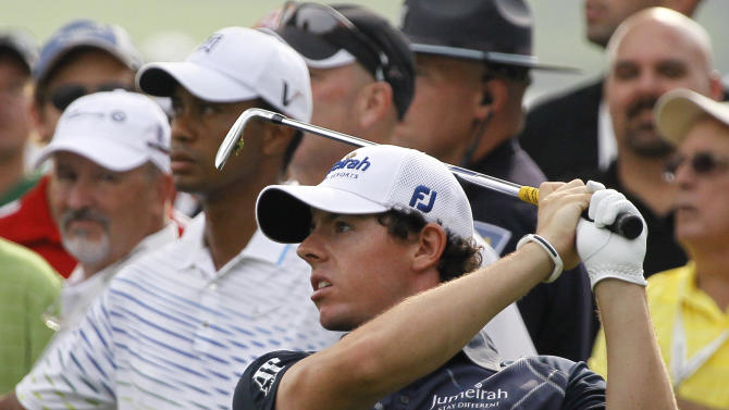 Rory McIlroy of Northern Ireland, tees off on the third hole as Tiger Woods looks on, during the second round of the BMW Championship PGA golf tournament at Crooked Stick Golf Club in Carmel, Ind., Friday, Sept. 7, 2012. (AP Photo/Charles Rex Arbogast)
