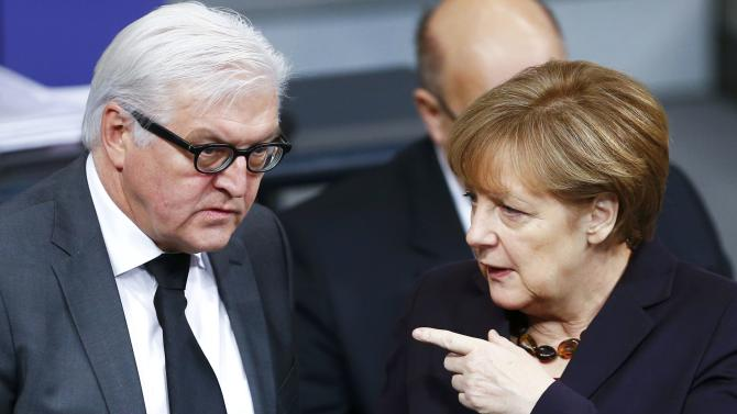 German Chancellor Merkel gestures next to Foreign Minister Steinmeier during a session of the lower house of parliament Bundestag in Berlin