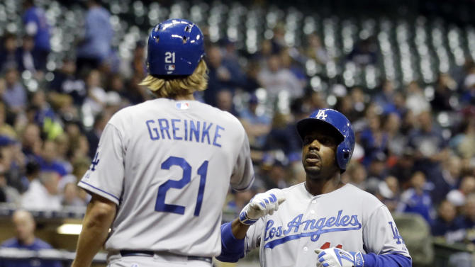 Los Angeles Dodgers' Jimmy Rollins is congratulated at home by Zack Greinke (21) after hitting a two-run home run during the seventh inning of a baseball game against the Milwaukee Brewers Tuesday, May 5, 2015, in Milwaukee. (AP Photo/Morry Gash)