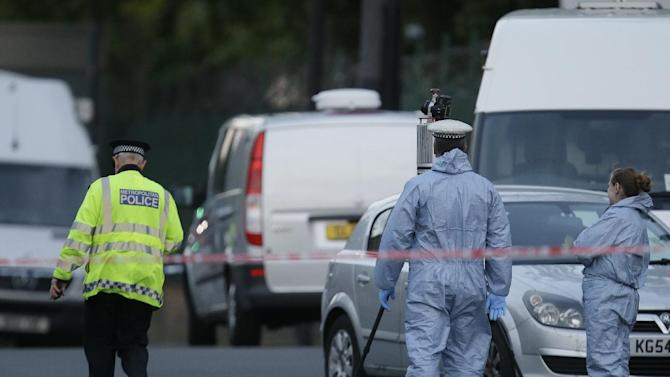 Police and forensic officers near the scene of an attack which has left one man confirmed dead and two people wounded near Woolwich barracks in London Wednesday, May, 22, 2013. Scotland Yard said officers responded to reports of an assault Wednesday afternoon in the London neighbourhood of Woolwich. London Ambulance service said one man was found dead at the scene and two other men were taken to the hospital, with one in serious condition.(AP Photo/Alastair Grant)