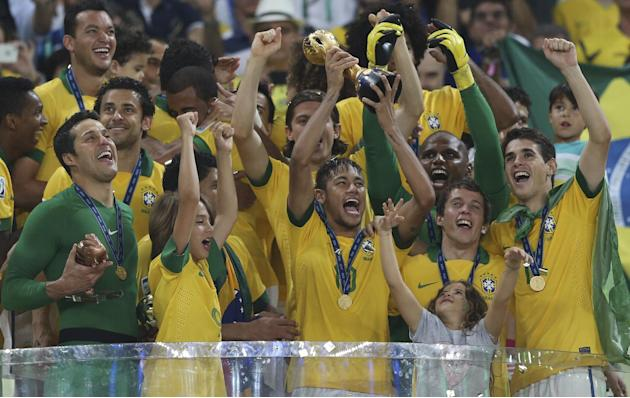 In this June 30, 2013 file photo, Brazil's Neymar lifts the trophy after the soccer Confederations Cup final against Spain at the Maracana stadium in Rio de Janeiro, Brazil. Brazil won 3-0