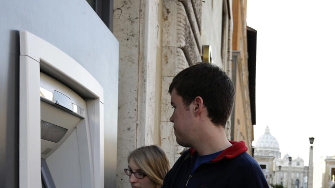 "Ben Kiniry, of Texas, gets cash from an ATM machine along Via della Conciliazione, the main road leading to St. Peter's Basilica at the Vatican, Thursday, Jan. 3, 2013. It's ""cash only"" now for tourists at the Vatican wanting to pay for museum tickets, souvenirs and other services after Italy's central bank decided to block electronic payments, including credit cards, at the tiny city state. The Italian daily Corriere della Sera reported Thursday that Bank of Italy took the action because the Holy See has not yet fully complied with European Union safeguards against money laundering. That means Italian banks are not authorized to operate within the Vatican, which is in the process of improving its mechanisms to combat laundering. The Vatican says it's scrambling to find a non-Italian bank to provide the electronic payment services ""quite soon"" but declined to discuss Bank of Italy's concerns. The central bank had no immediate comment on the situation. (AP Photo/Alessandra Tarantino)"