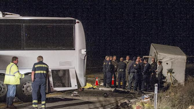 San Bernardino County Fire Department officers and police officers investigate the accident where at least eight people were killed and 38 people were injured after a tour bus carrying a group from Tijuana, Mexico crashed with two other vehicles near Yucaipa, Calif., Sunday, Feb. 3, 2013. (AP Photo/Ringo H.W. Chiu)