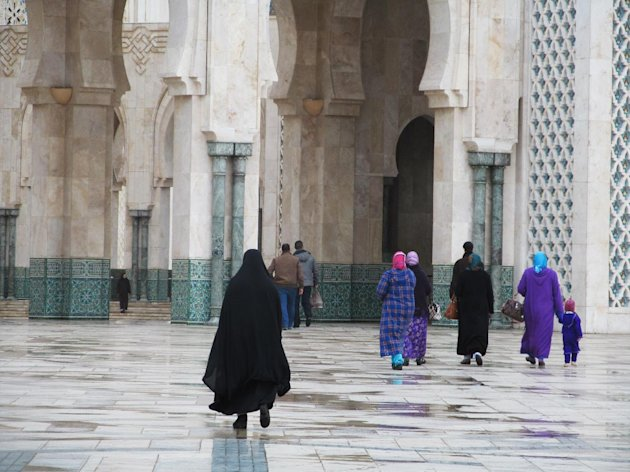 Women about to enter Casablanc's monumental Hassan II mosque in Morocco.