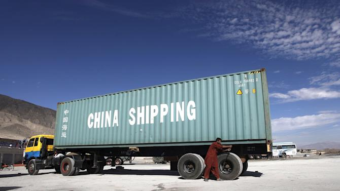 A worker tightens the wheels on a truck carrying a shipping container outside Quetta